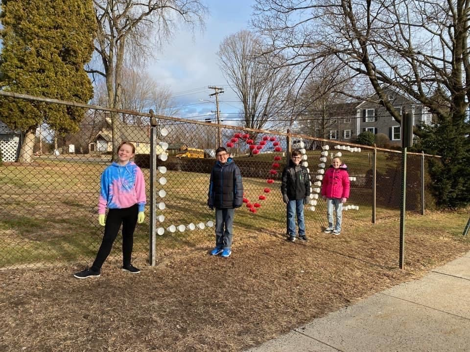 KIM students putting cups in chain link fence